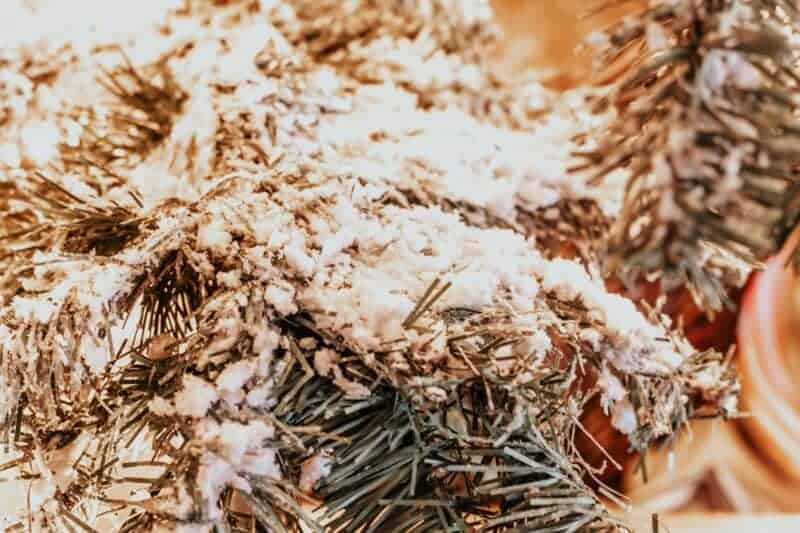 Close up of flocked Christmas tree branch on a farmhouse artificial Christmas tree.