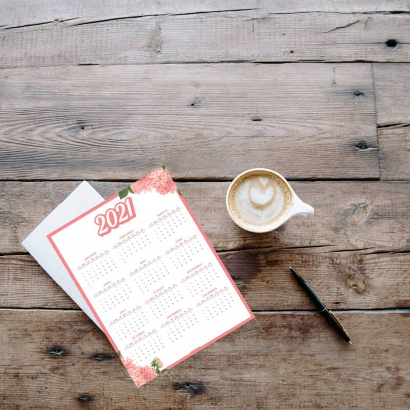 Wooden table with 2021 Calendar on top and a cup of coffee