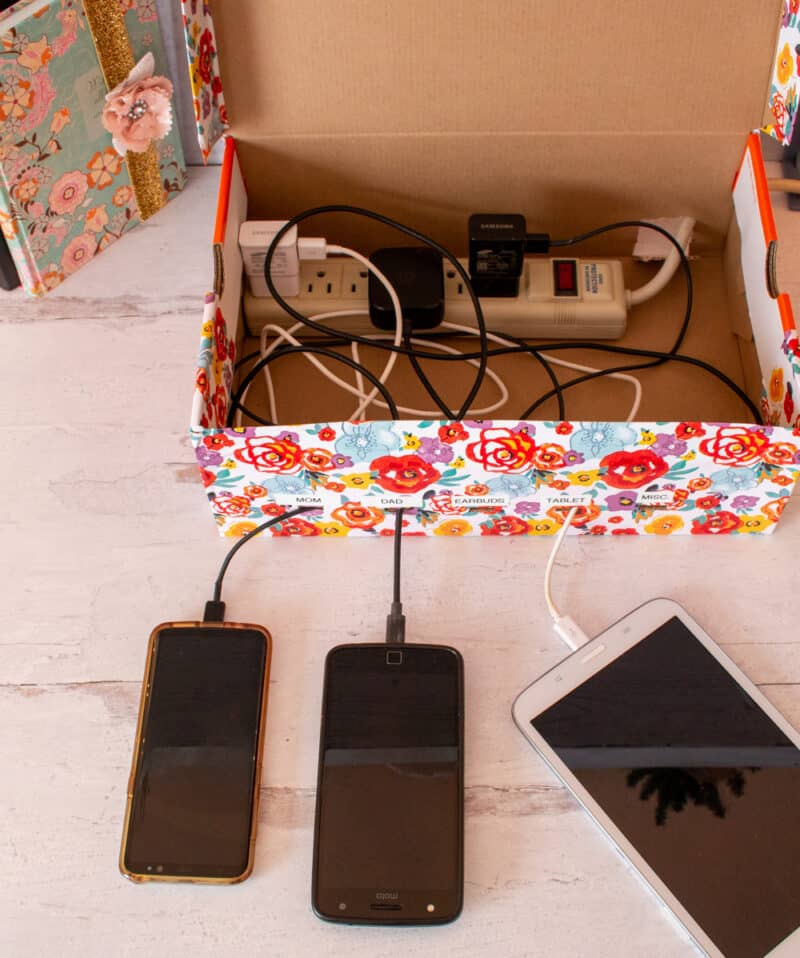 Overhead view of inside of DIY shoebox charging station with cords and Samsung Smartphone and tablet attached and charging.