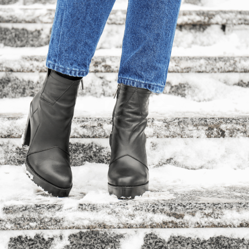 black leather women's boots in snow