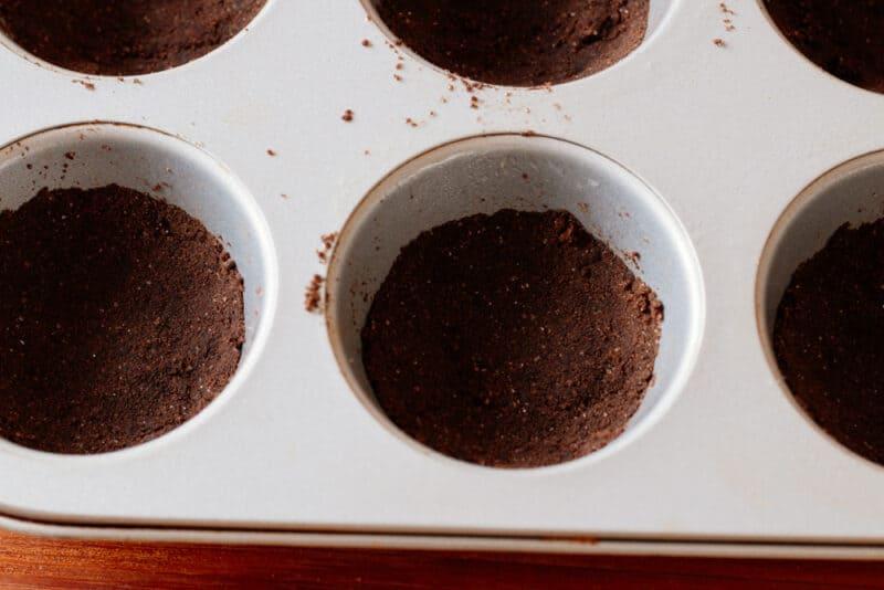homemade chocolate pie crust in bottom of cupcake pan