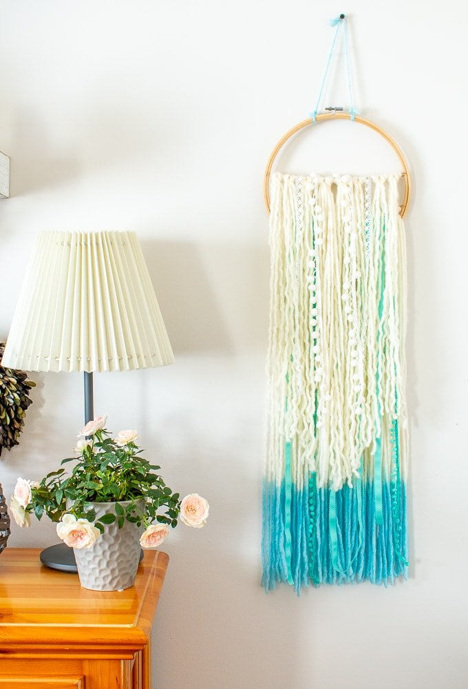 DIY Yarn Boho Wall Hanging on White Wall next to pot of mini pink roses