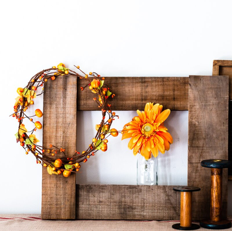Pallet wood picture frame on buffet with autumn wreath, orange flower in glass vase, and vintage wooden spools