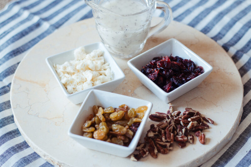 Ingredients for a spiralized apple salad. Containers of feta cheese, golden raisins, dried cranberries, and pecans.