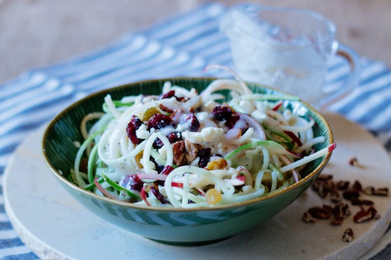Green glass bowl filled with a spiralized apple salad.