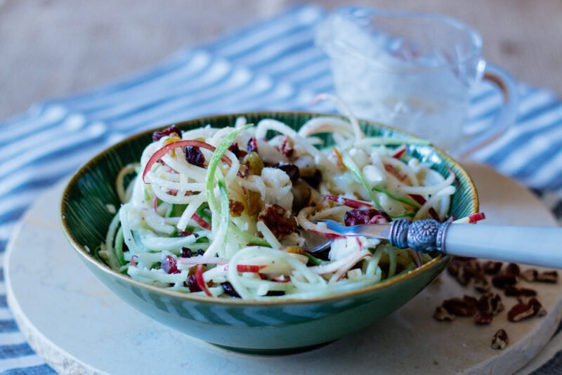Bowl filled with a spiralized apple salad and a Pioneer Woman fork.