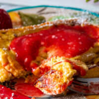 Pioneer Woman plate with two slices of fresh homemade French Toast garnished with homemade strawberry syrup - strawberry puree