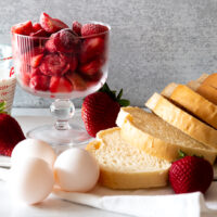 Ingredients for homemade French Toast and Strawberry Syrup Puree - thick sliced bread, eggs, milk, and strawberries in a glass compote bowl