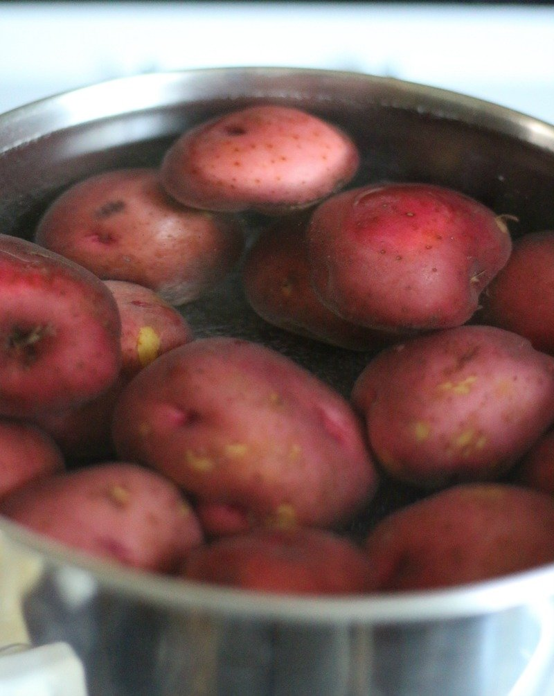 Large pot on stove filled with red potatoes being cooked for Grandma's Old Fashioned Potato Salad recipe