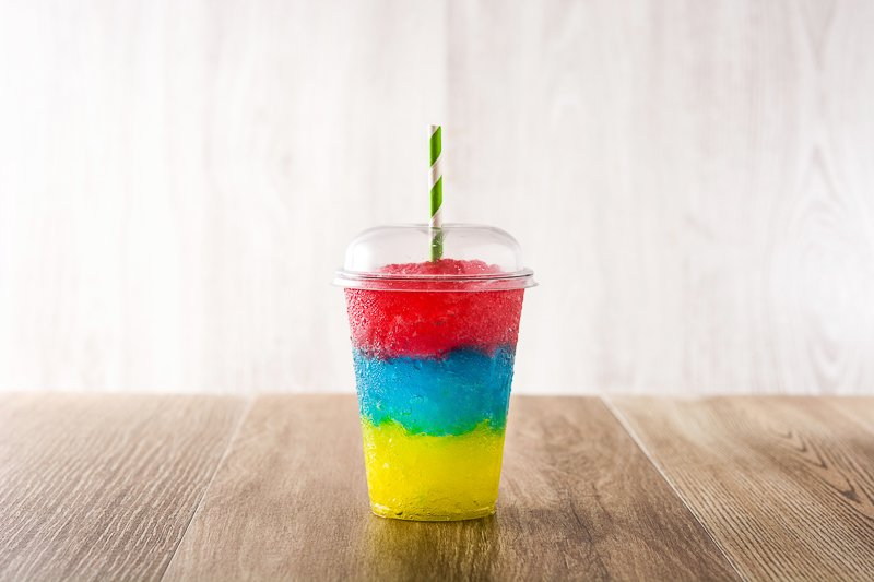 Homemade Slushie reci- 3 layered in a clear plastic cup with straw - front view