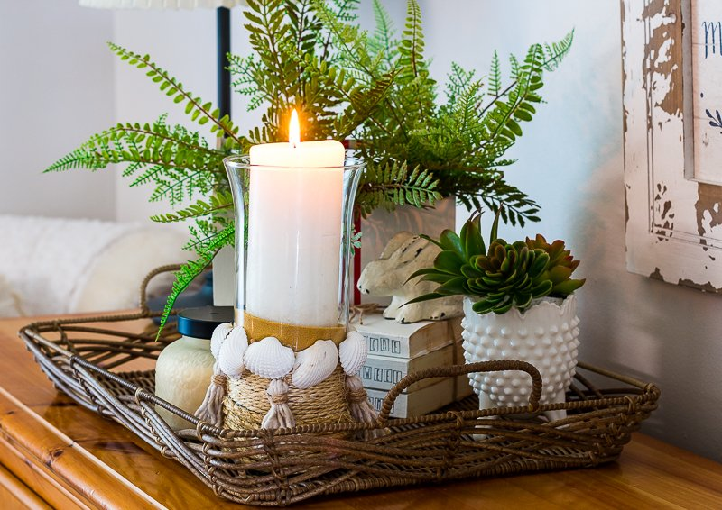 DIY seashell candle holder in a basket on a buffet.