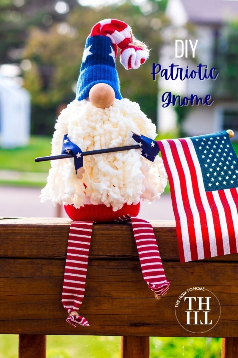 Cute little patriotic sock gnome sitting on a railing holding an American Flag