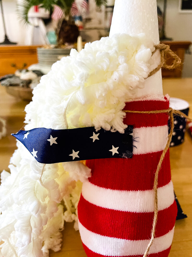 Side view of patriotic gnome with arms being attached