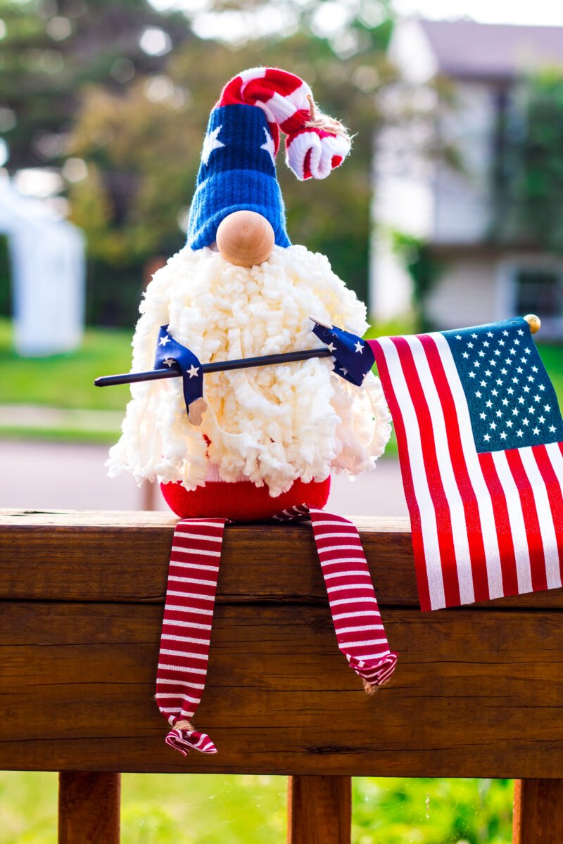 Adorable Patriotic Gnome with a fluffy yarn bear and a body made from a sock sitting on an outdoor porch railing holding an American Flag