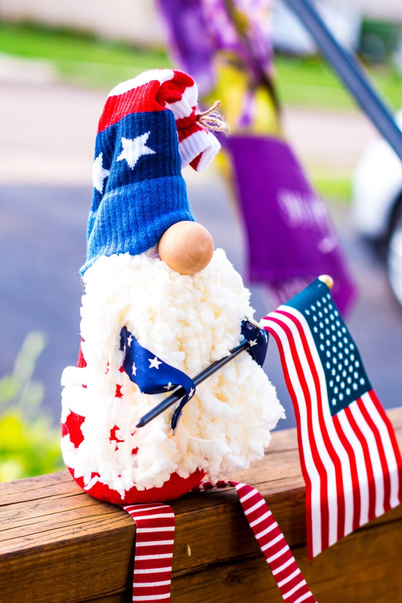 DIY Patriotic Gnome holding an American Flag and Sitting on a wooden porch railing