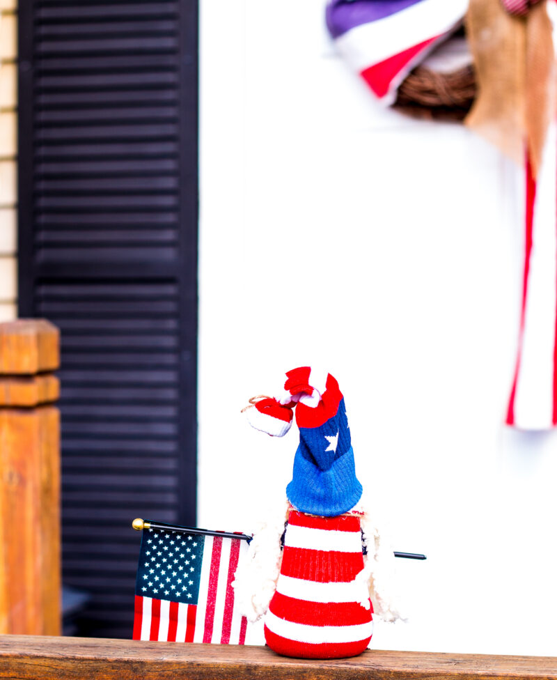 Back view of patriotic gnome holding an American Flag looking at an old glory DIY American Flag front door wreath
