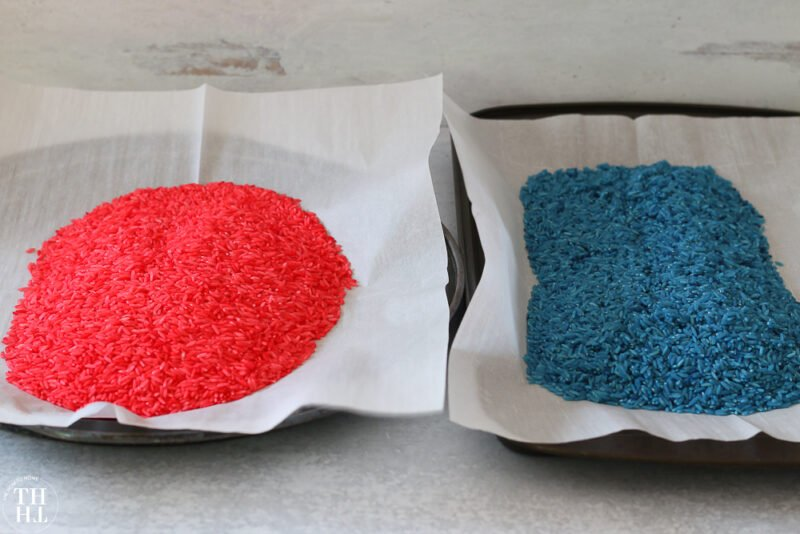 Red and Blue dyed rice on cookie sheets lined with parchment paper