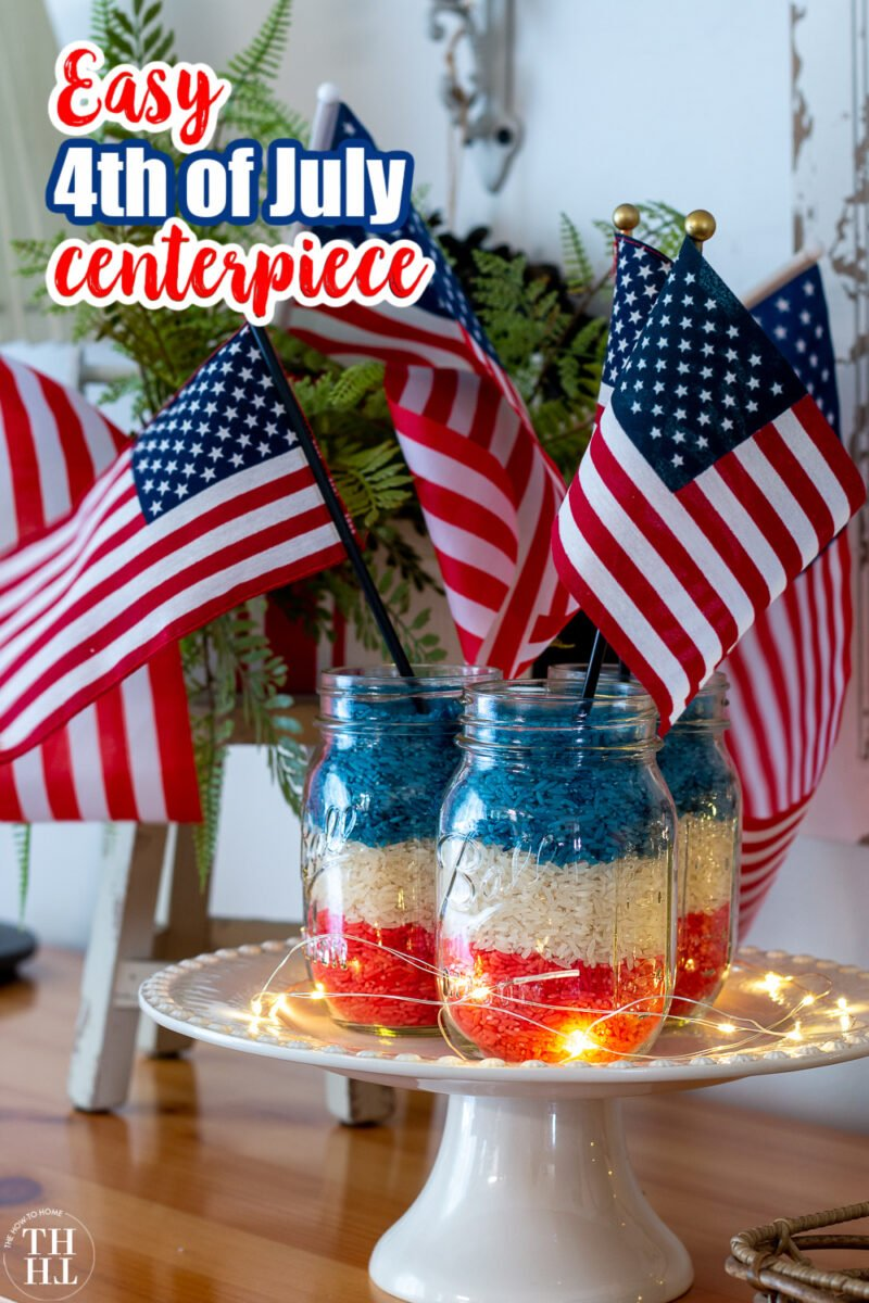 Three mason jars filled with red white and blue rice on a white cake plate with small American Flags in each Jar - a 4th of July Centerpiece