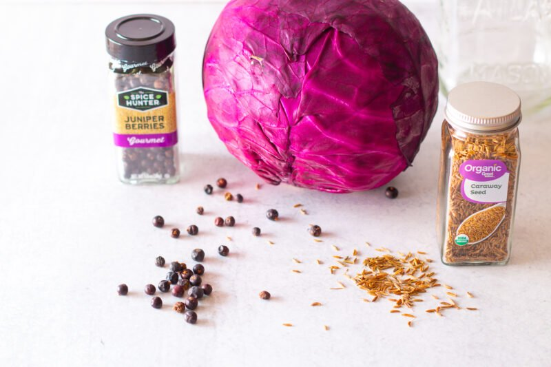 Ingredients used to make red cabbage sauerkraut in a mason jar - fresh head of red cabbage, juniper berries, and caraway seeds