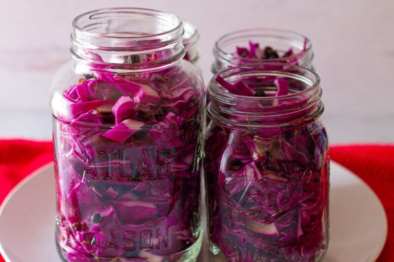 Shredded cabbage in mason jar waiting for brine to be added for homemade red cabbage sauerkraut