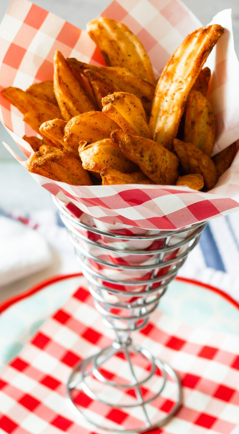 Metal diner style wire cone basket with red and white checked liner filled with air fryer frozen steak fries crisped to perfection!