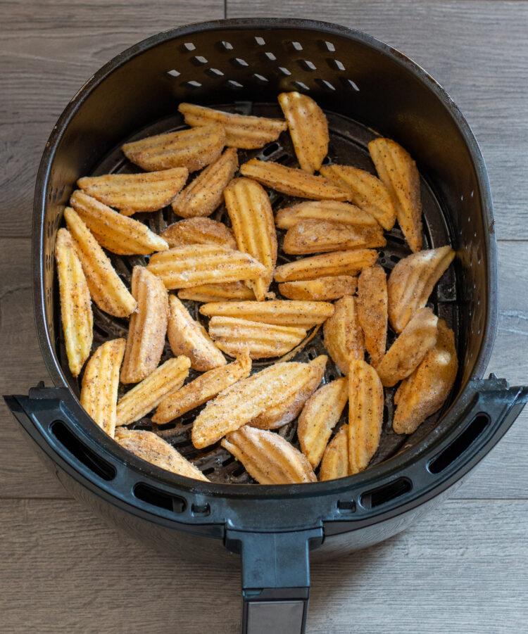 Single layer of frozen steak fries in air fryer basket - overhead view