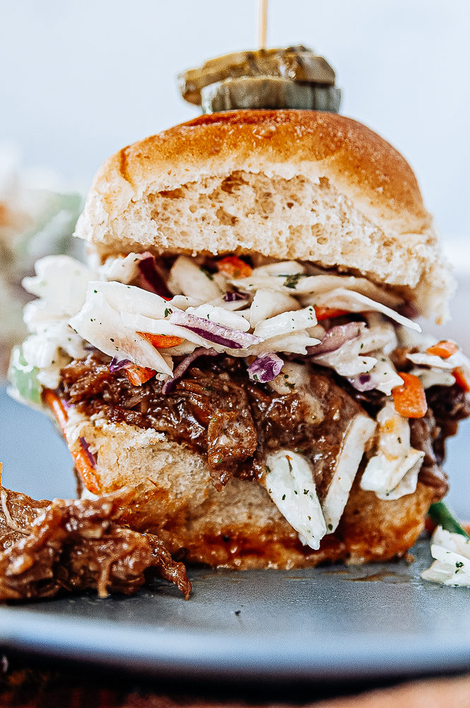 close up view of a slow cooker pulled porch sandwich topped with fresh apple slaw on a bun with a pickle skewer on top