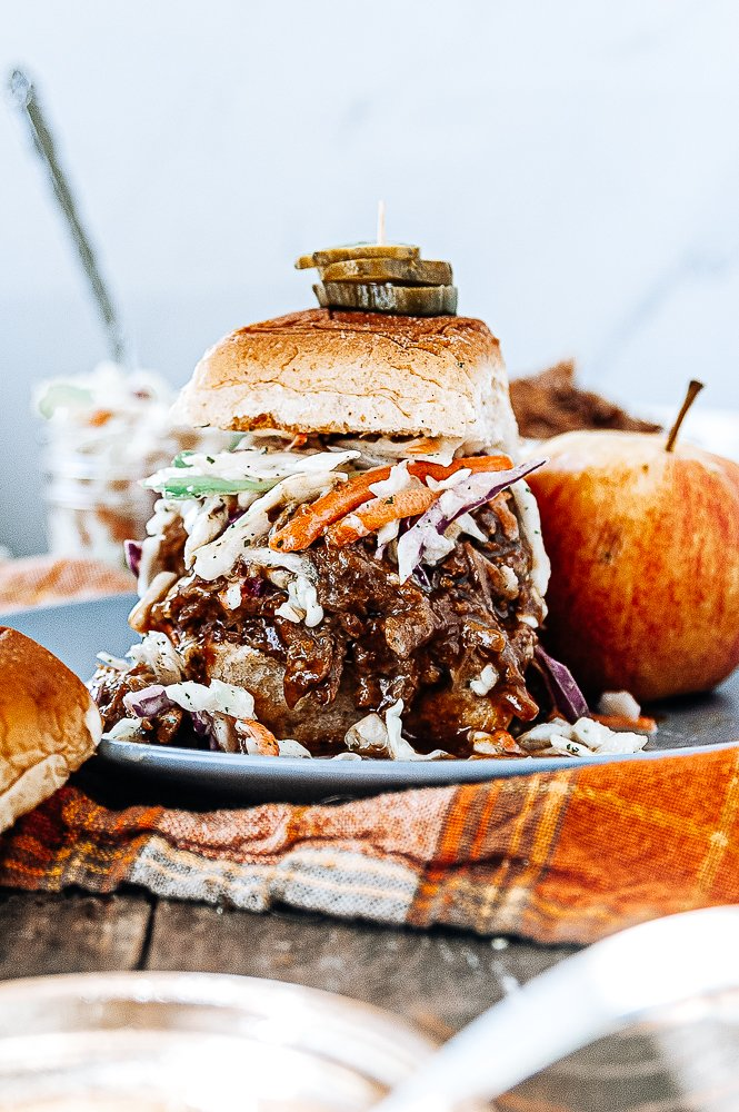 Side view of a yummy tall stacked crock pot pulled pork sandwich on a plate with apple slaw on top and a stack of three pickle slices