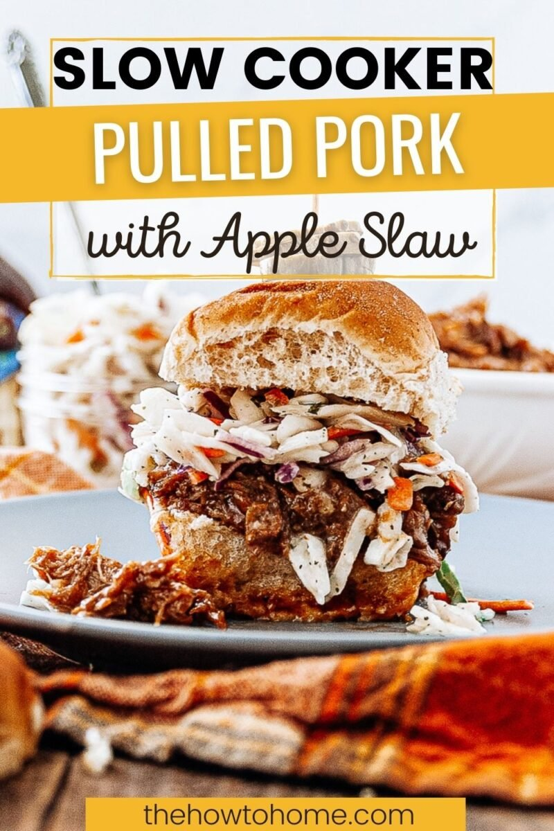 Pinterest image of a pulled pork sandwich topped with apple slaw on a bun with a spear of pickle slices on top