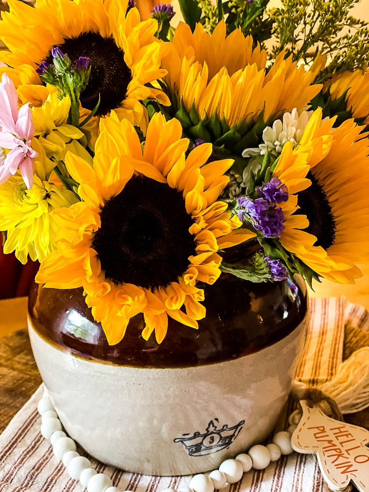 Vintage bean pot filled with fresh sunflowers