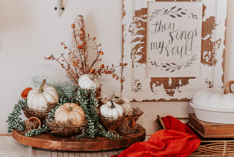 Front view of a rustic lazy susan topped with Pink Depression Glass filled with Spanish moss and faux and real pumpkins for an autumn display and a side display