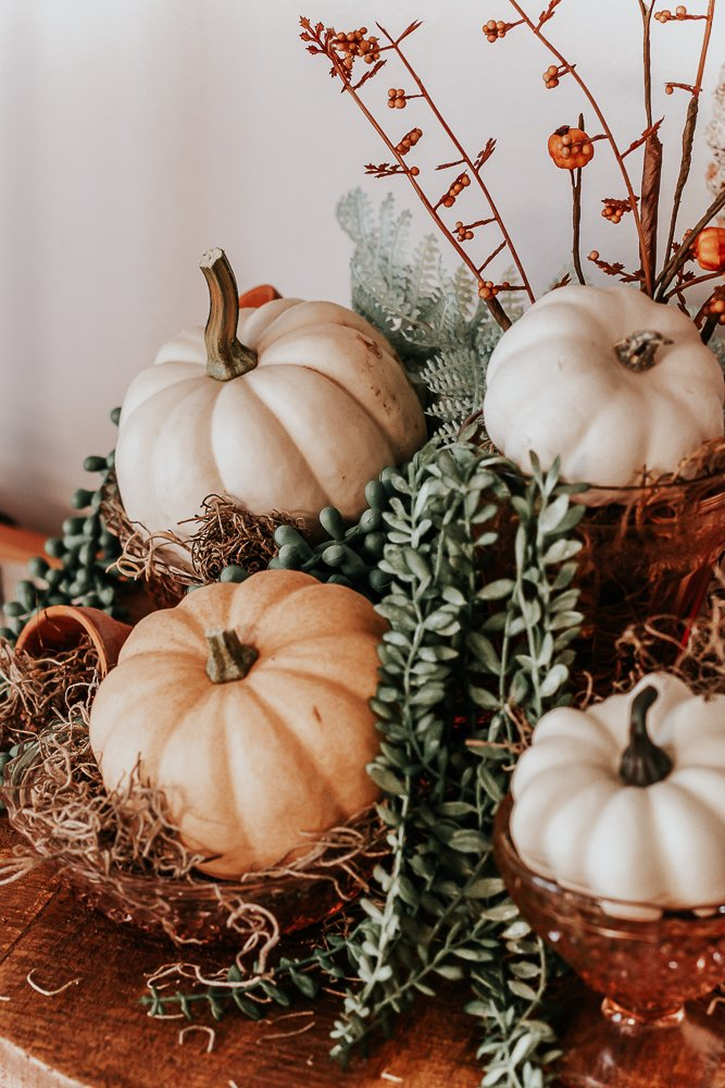 close up view of pink depression glass filled with white and pale orange pumpkins, greenery, and faux greens for an autumn display made with depression glass