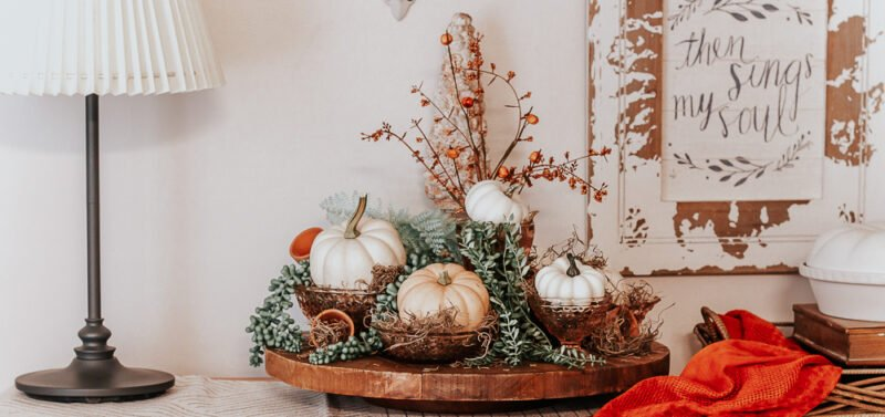 Front view of a rustic lazy susan topped with Pink Depression Glass filled with Spanish moss and faux and real pumpkins for an autumn display